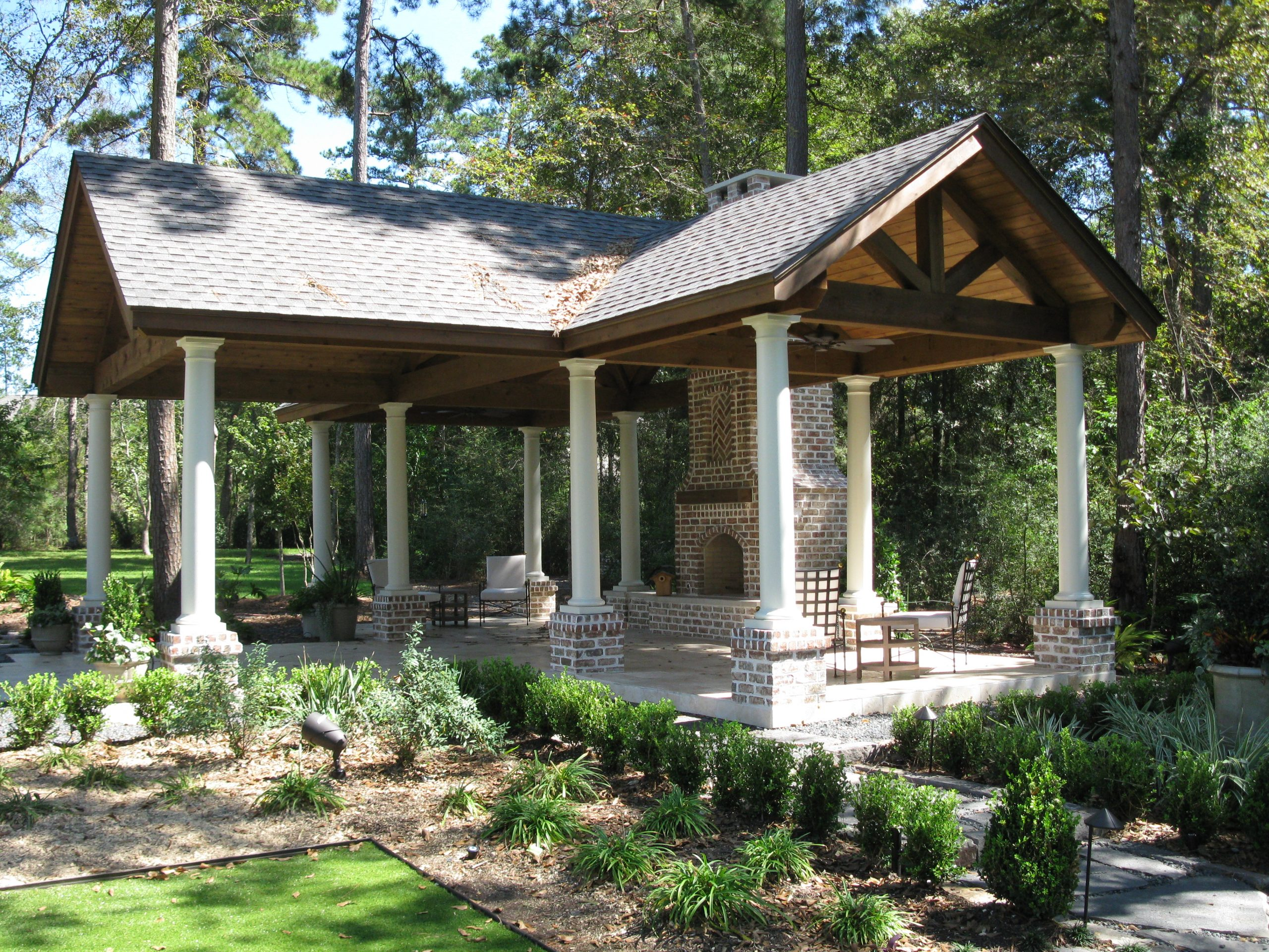 Side view of beautiful custom timber truss covered patio and landscaping.