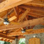 Underside of fans and lighting installed in poolside cover patio.